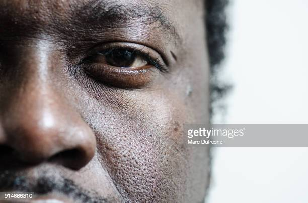 close up on the left eye and nose of a black young adult man - black eye stock pictures, royalty-free photos & images