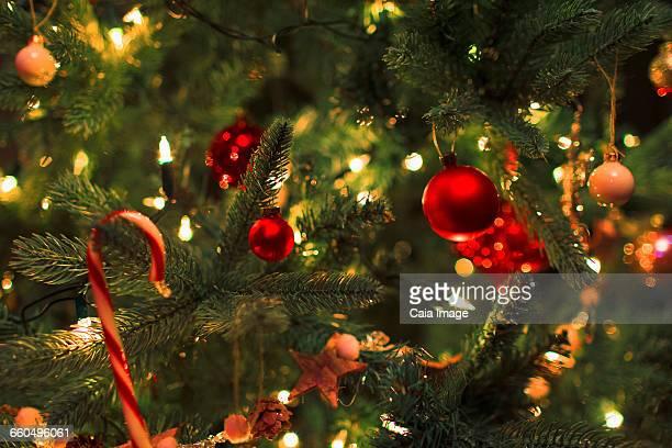 close up ornaments and string lights on christmas tree - albero di natale foto e immagini stock