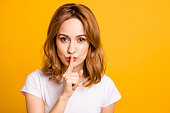 Close up photo beautiful amazing she her foxy lady hold arm hand index finger mouth lips ask stop talking tell speak say secrecy information wear casual white t-shirt isolated yellow background