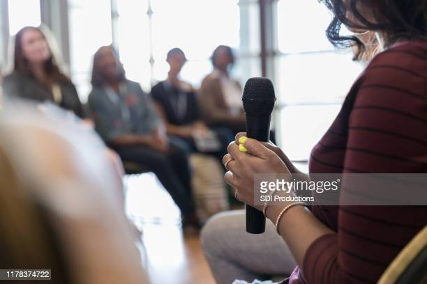 close up photo female human hands holding microphone - panel discussion stock pictures, royalty-free photos & images
