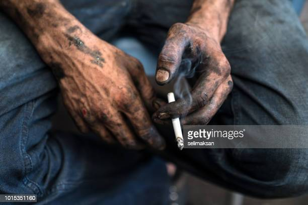 Close Up Photo Of Blue Collar Worker's Hands Holding Cigarette