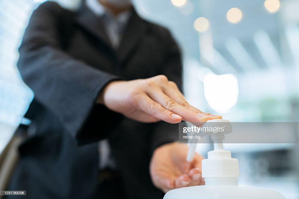 オフィスビルのエントランスホールでアルコールハンド消毒剤を塗布するビジネスウーマンの写真をクローズアップ : ストックフォト