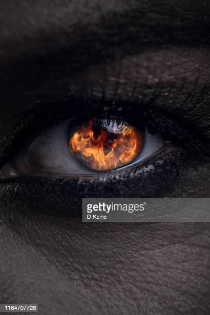 close up photo of female eye with fire reflection - demonio imagens e fotografias de stock