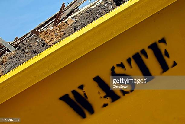 Close up photo of yellow construction dumpster reading WASTE