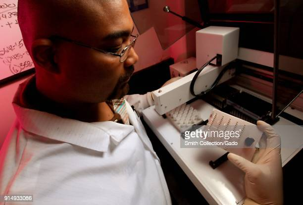 Close up photograph of the CDC biologist Damian Danavall and a NCHHSTP staff member working in a laboratory setting up a machine for handling liquids...