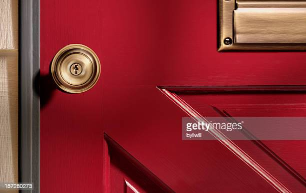 Close up picture of a doorknob on a red door