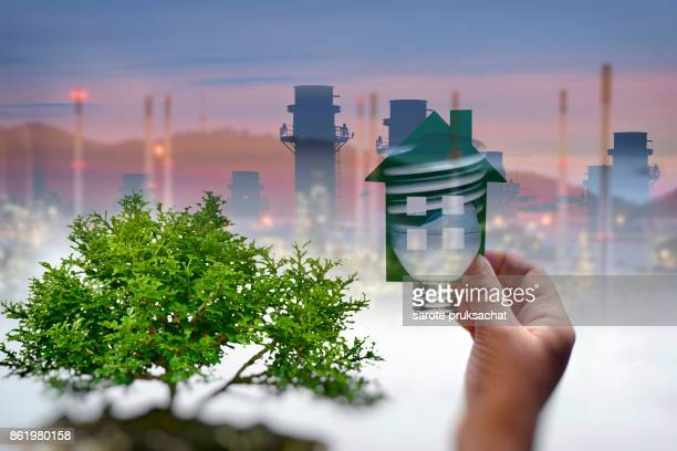 close up picture of  boy hands holding green house and industry background . save energy concept