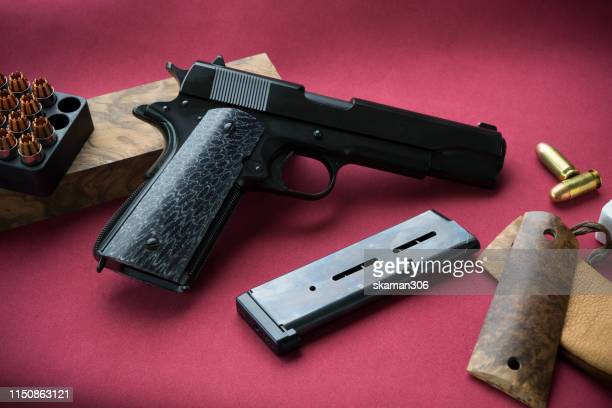 close up pistol gun barrel and wooden and dark black ground - ammunition magazine stock photos and pictures