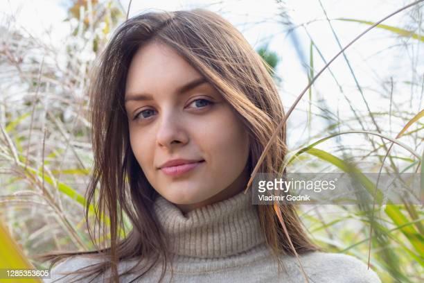 close up portrait beautiful young brunette woman in tall grass - brune aux yeux bleus photos et images de collection