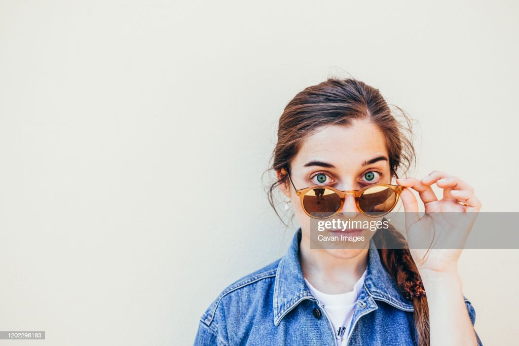 Close up portrait of a beautiful young woman with green eyes looking at the camera on a yellow background : Stock Photo