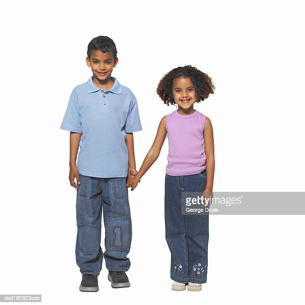 Close up portrait of a boy (10-11) and girl (8-9) holding hands