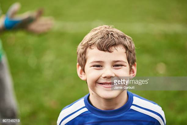 Close up portrait of a child smiling at football