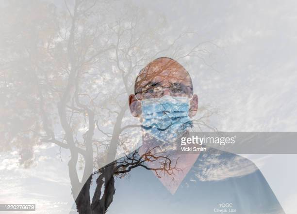 close up portrait of a male health care worker wearing a blue face mask - essential workers stock pictures, royalty-free photos & images