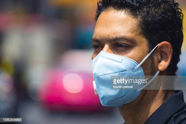 close up portrait of a man using pm 2.5 pollution mask in the street of a big city . - air pollution stock pictures, royalty-free photos & images