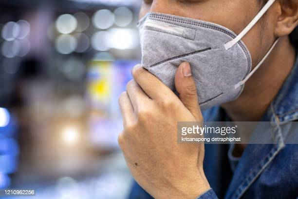 close up portrait of a man using pm 2.5 pollution mask in the street of a big city - respirator mask stock pictures, royalty-free photos & images