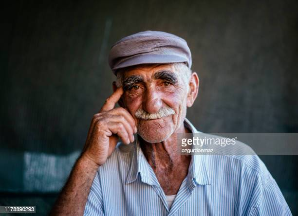 close up portrait of a senior man over dark background - anatolia stock pictures, royalty-free photos & images