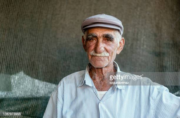 close up portrait of a senior man over dark background - kurdish ethnicity stock pictures, royalty-free photos & images