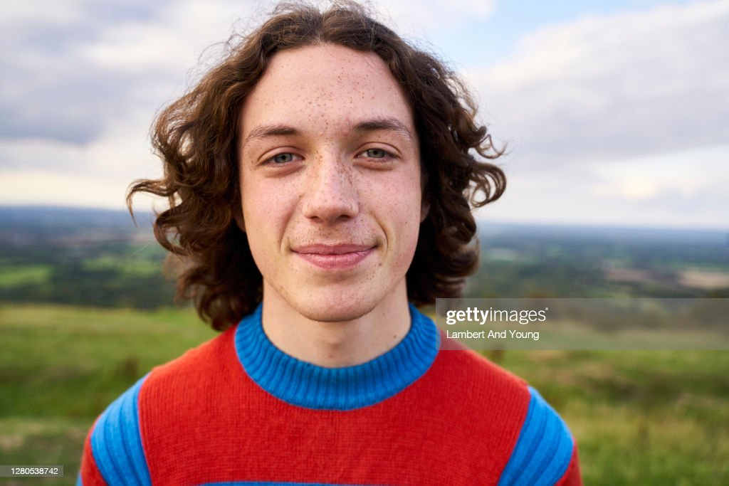 Close up portrait of a teenager looking to the camera in the outdoors : Stock Photo