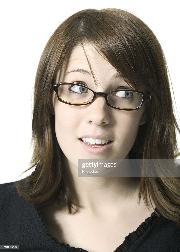 close up portrait of a young adult female in a black shirt and glasses as she playfully rolls her eyes : Foto de stock