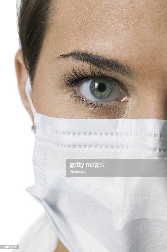 close up portrait of a young adult female nurse in a mask as she looks at the camera : Foto de stock