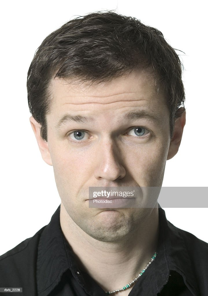 close up portrait of a young adult male in a black shirt as he frowns at the camera : Foto de stock