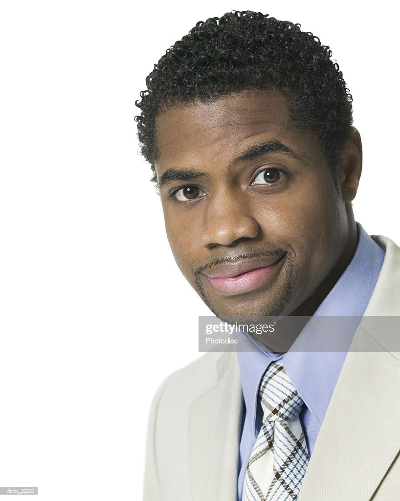 close up portrait of a young adult male in a light suit as he smiles confidently : Foto de stock
