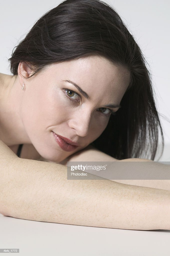 close up portrait of a young adult woman as she lays down on her arms : Stockfoto