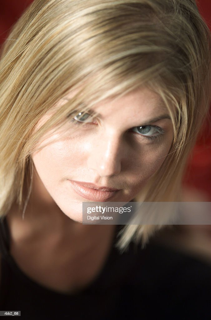 close up portrait of a young caucasian blonde woman in a black tank top as she seriously looks up into the camera : Stockfoto