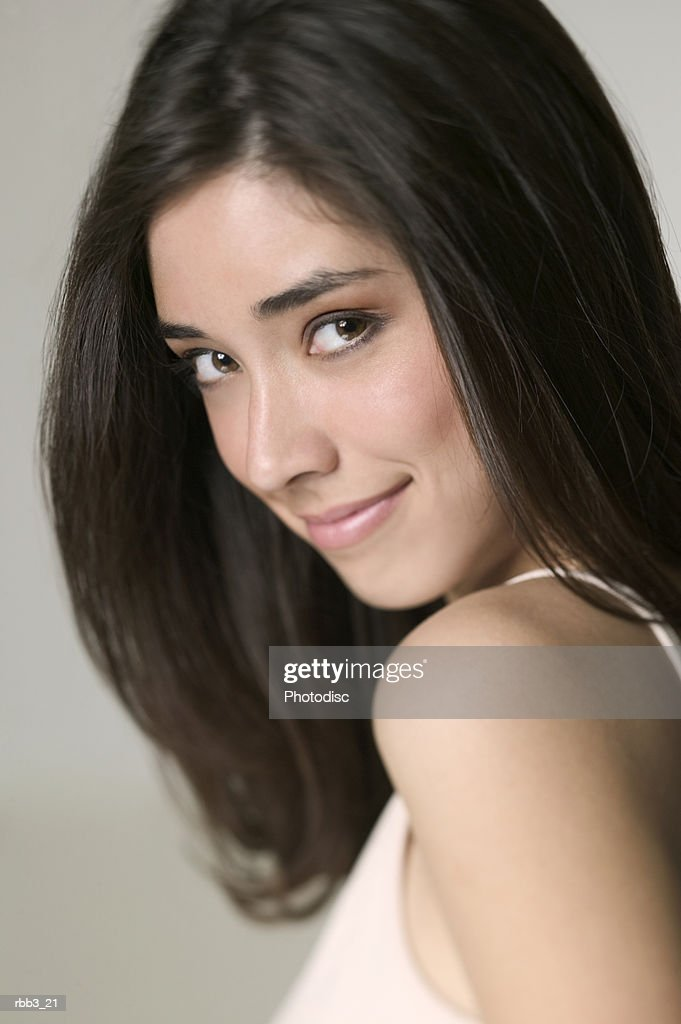 close up portrait of a young ethnic woman as she turns and smiles : Stockfoto