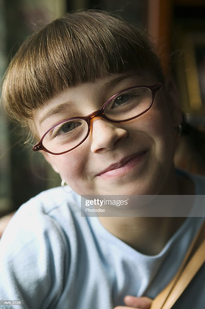 close up portrait of a young female child in glasses as she smiles at the camera : Stockfoto