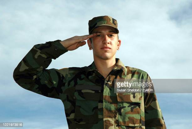 close up portrait of a young male soldier standing at attention - saluting stock pictures, royalty-free photos & images