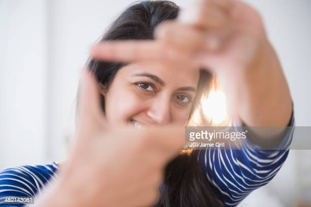 Close up portrait of Asian woman making finger frame