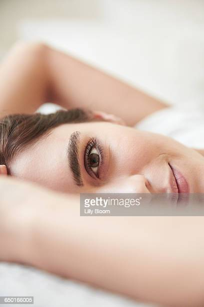 Close up portrait of beautiful young woman lying on bed