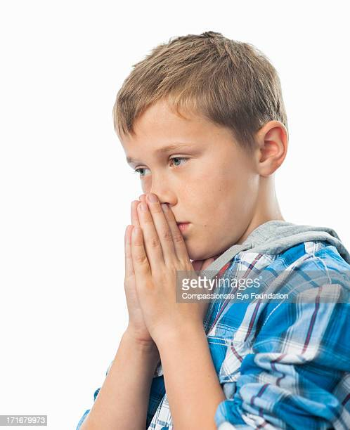 Close up portrait of boy (9-11) praying