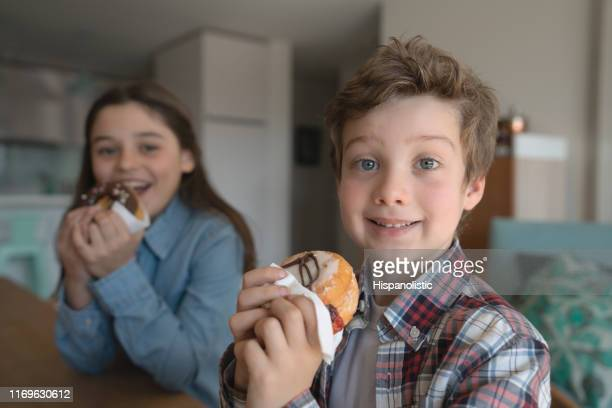 close up portrait of brother and sister at home enjoying delcious donuts while facing camera smiling - fat people eating donuts stock pictures, royalty-free photos & images