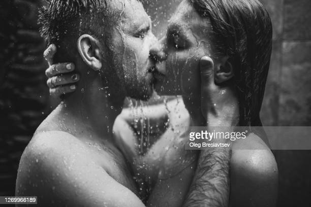 close up portrait of couple in love kissing under tropical shower with passion. intimate, togetherness and romantic. black and white. - marriage stock pictures, royalty-free photos & images