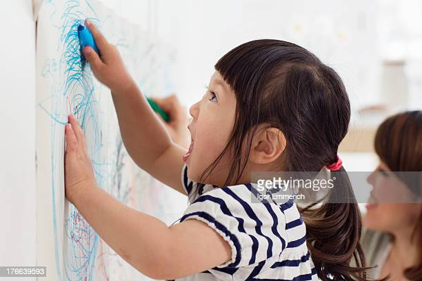 Close up portrait of female toddler having fun drawing
