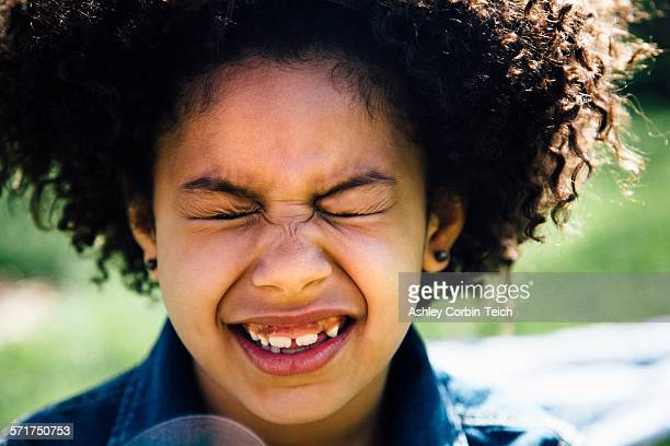 Close up portrait of girl with eyes closed pulling face