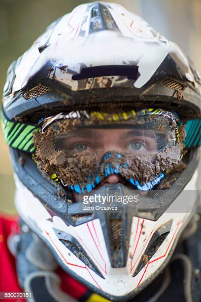 close up portrait of male motocross racer wearing muddy helmet and goggles - capacete capacete esportivo - fotografias e filmes do acervo