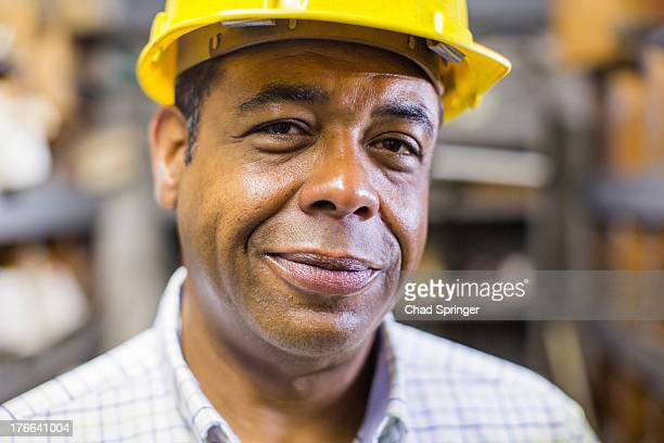 Close up portrait of man in stockroom wearing hard hat
