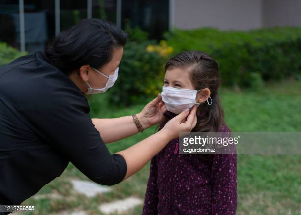 close up portrait of mother and daughter wear face mask to  to protect against coronavirus and flu outbreak - surgical mask stock pictures, royalty-free photos & images