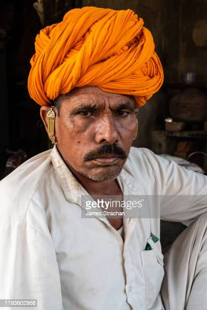 close up portrait of one mid adult male gujar villager in traditional white tunic and bright orange turban resting in the shade, pushkar, rajasthan, india (model release) - james strachan stock pictures, royalty-free photos & images