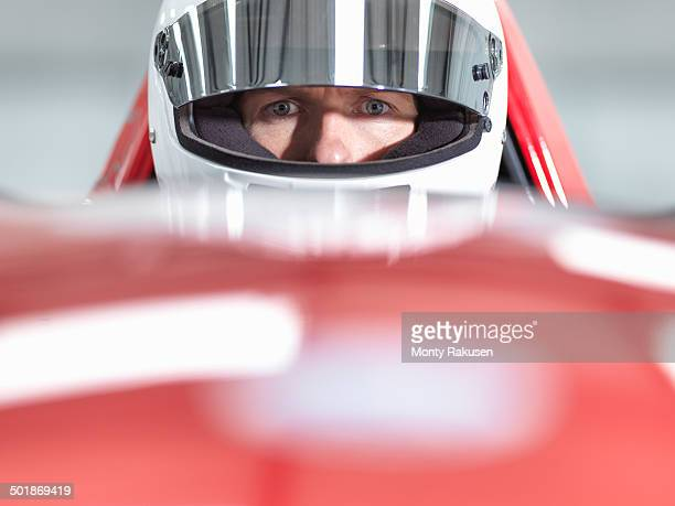 Close up portrait of racing car driver wearing helmet in supercar
