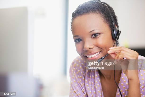 Cerrar el retrato de Empresaria sonriente con auricular