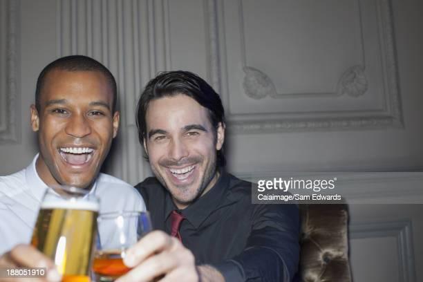 Gros plan portrait de souriant homme portant un toast à bière et à cocktail