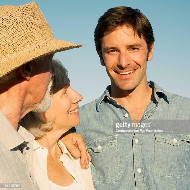"close up portrait of smiling senior couple and man - ""compassionate eye"" foto e immagini stock"