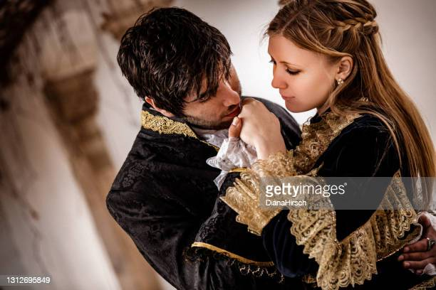 close up portrait of the handsome romeo kissing the beautiful juliets hand - princess stock pictures, royalty-free photos & images