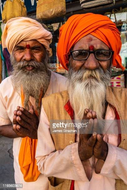close up portrait of two senior male pilgrims, with turbans and bushy beards, saying namaste, the customary hindu greeting usually spoken with a slight bow and hands pressed together, palms touching and fingers pointing upwards, thumbs close to the chest, - james strachan stock pictures, royalty-free photos & images
