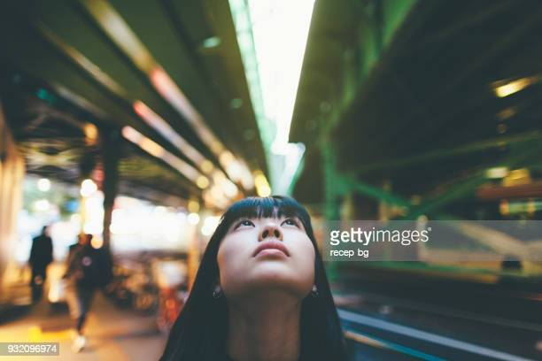 close up portrait of woman while loo0king up in the city - differential focus stock pictures, royalty-free photos & images