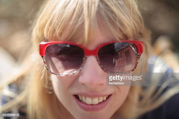 close up portrait of woman with house exterior reflected in sunglasses - heshphoto stockfoto's en -beelden